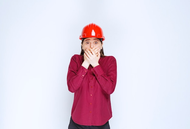 Beautiful female architect in red hard helmet scared of something.