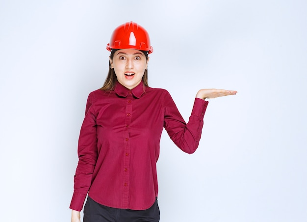 Beautiful female architect in red helmet standing and holding open space.