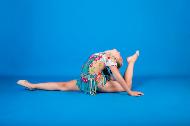 A beautiful female athlete in a gymnastic costume performs a longitudinal split with her leg raised up on a blue wall