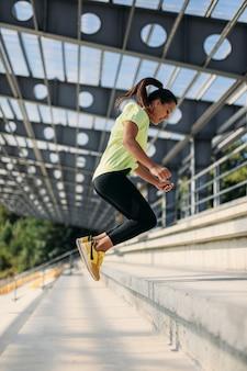 階段で運動しながらジャンプするアクティブウェアの美しい女性アスリート。屋外の晴れた日にスポーツ活動を楽しんでいる健康で若い女性。