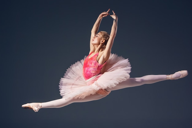 Beautiful female ballet dancer on a grey background