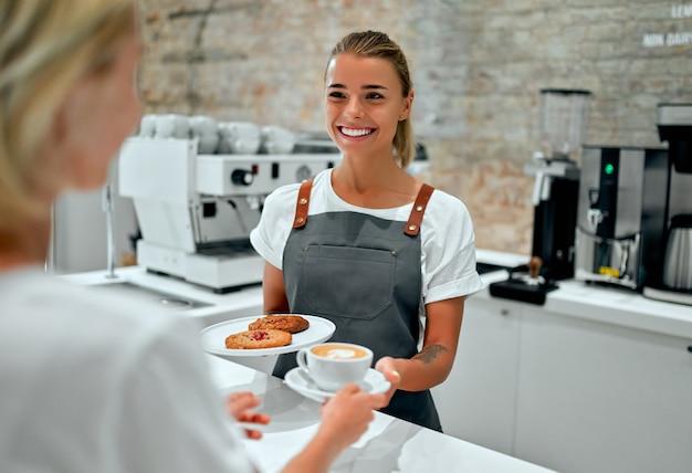 Красивая женщина-бариста дает чашку кофе или капучино и тарелку печенья клиенту в кафе.