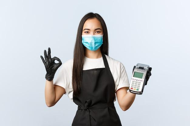 Красивая женская бариста в черном фартуке с маской для лица