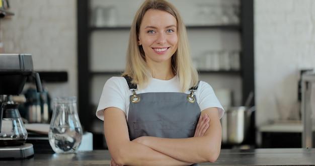 아름다운 여성 바리스타는 커피숍 바에서 행복한 미소를 짓고 있습니다. 레스토랑의 아늑한 로프트 스타일 카페 카운터 뒤에 있는 행복한 직원의 초상화.