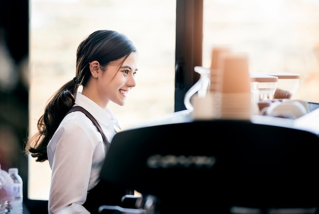 Beautiful female barista in uniform standing and working with coffee machine.