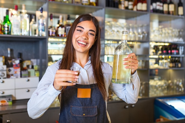 Beautiful female bartender is holding a shot glass with alcohol drink and a bottle in other hand