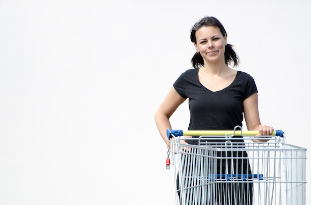 Beautiful female in a black shirt holding a shopping cart on white