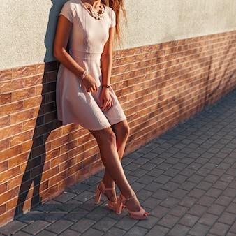 Красивое женское тело в розовом платье на каблуках у кирпичной стены