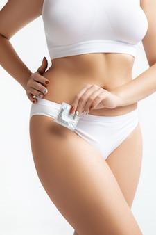 흰색 배경에 고립 된 속옷에 아름 다운 여성의 몸. 바디 케어 및 리프팅, 교정 수술, 미용 및 완벽한 피부, 건강한 라이프 스타일, 안전의 개념. 콘돔을 들고.