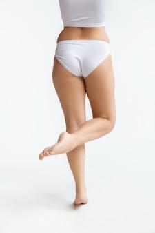 흰색 배경에 고립 된 속옷에 아름 다운 여성의 몸. 바디 케어 및 리프팅, 교정 수술, 미용 및 완벽한 피부, 체중 감소, 다이어트의 개념. 자신감 포즈, 다시보기.