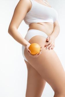 흰색 배경에 고립 된 속옷에 아름 다운 여성의 몸. 바디 케어 및 리프팅, 교정 수술, 미용 및 완벽한 피부, 체중 감소, 다이어트의 개념. 오렌지를 들고. 건강한 식생활.