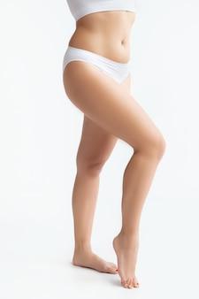 흰색 배경에 고립 된 속옷에 아름 다운 여성의 몸. 바디 케어 및 리프팅, 교정 수술, 미용 및 완벽한 피부, 체중 감소, 다이어트의 개념. 자신감있는 자세로 다리를 보여줍니다.