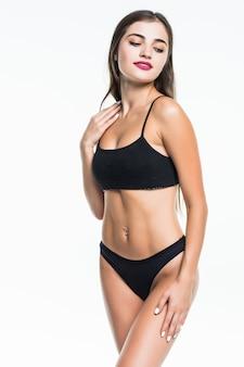 美しい女性の身体は白で隔離されます。分離された黒の下着でセクシーな若い女性