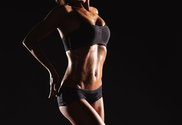 暗い背景のアスリートの美しい女性の体