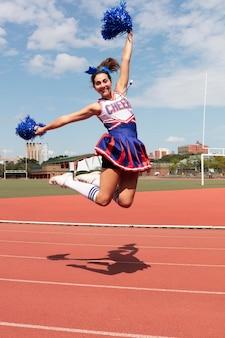 Bella cheerleader femminile in uniforme carina