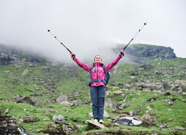 Beautiful female climber lifting hands up in the air with walking sticks in hands while standing on rock admiring the beauty of green rocky foggy mountains