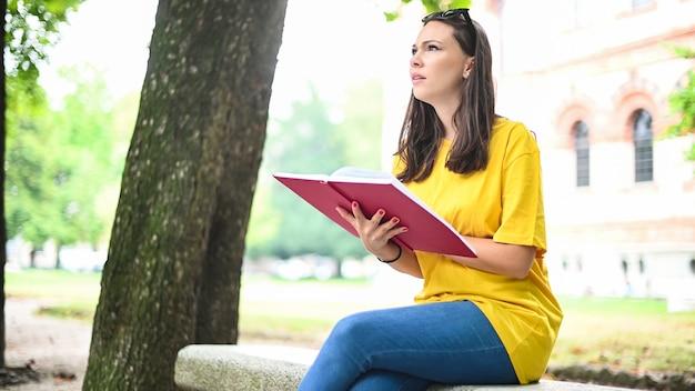 公園のベンチで本を読んでいる美しい女子大生