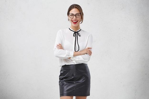 Bella studentessa universitaria indossa abiti bianchi e neri, ha un'occasione speciale, tiene le mani giunte, guarda con sicurezza