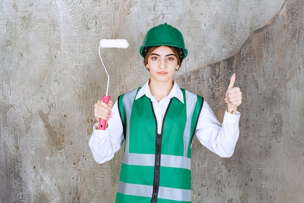 Beautiful female construction worker holding painting roll and showing thumbs up