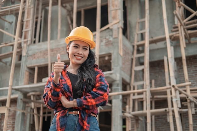Beautiful female contractor with thumbs up wearing a safety helmet in the background of building construction