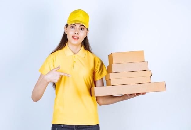 Красивый женский курьер, держащий картонные коробки и стоящий на белом.