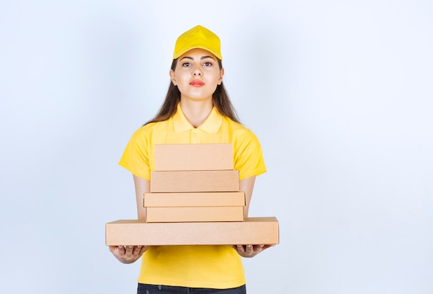 Beautiful female courier holding carton boxes and looking at camera over white wall.