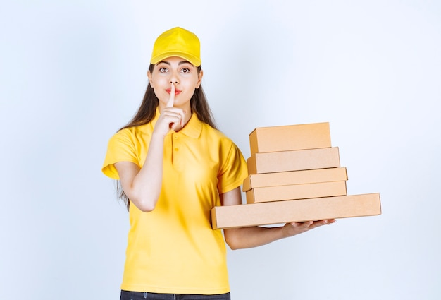 Красивый женский курьер, держащий картонные коробки на белом.