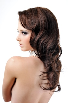 Beautiful female curly long hairs - back view on white wall