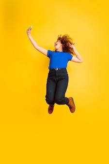 美しい女性の巻き毛モデルのジャンプ