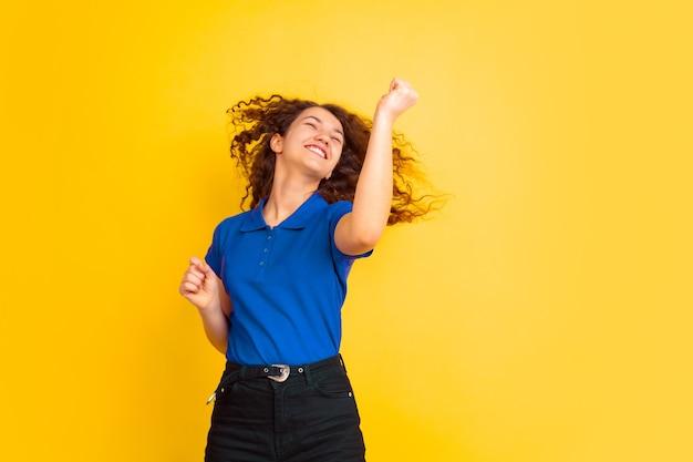 노란색 스튜디오 벽에 아름 다운 여성 곱슬 모델입니다.