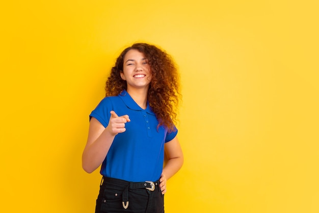 Beautiful female curly model in shirt pointing