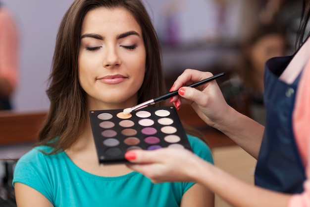 Beautiful female customer during the work of makeup artist