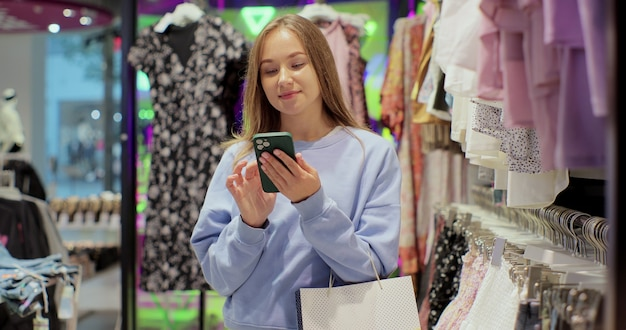 Beautiful female customer shopping in clothing store, using smartphone, browsing online, comparing on internet, choosing stylish clothes.