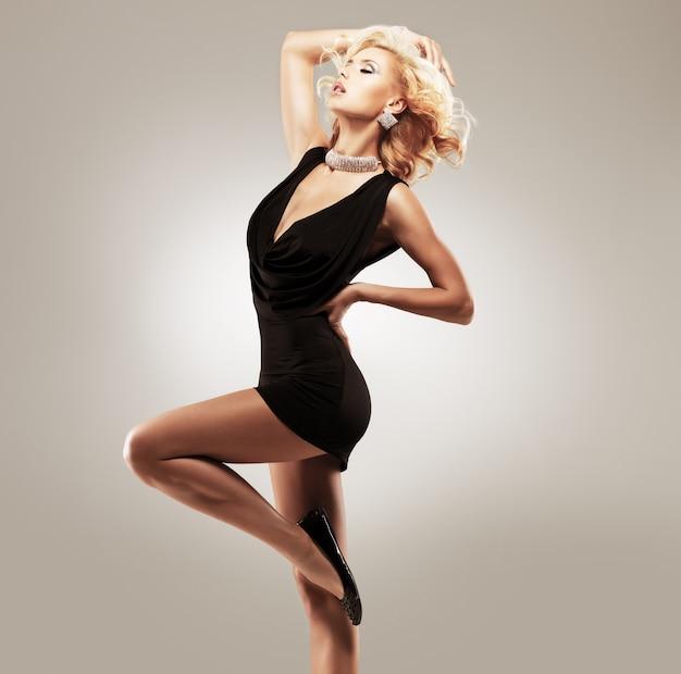 Bella ballerina in abito nero che propone allo studio