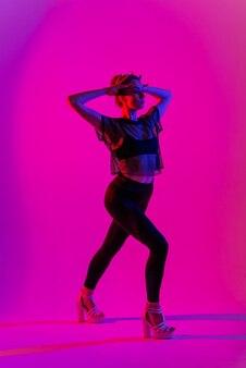 ポール ダンス トリック、ネオンを実行しながら黒とハイヒールを着ている美しい女性ダンサー