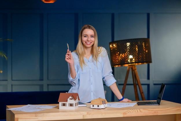 Beautiful female designer in modern blue office.