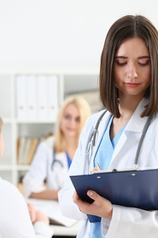 Beautiful female doctor holding clipboard