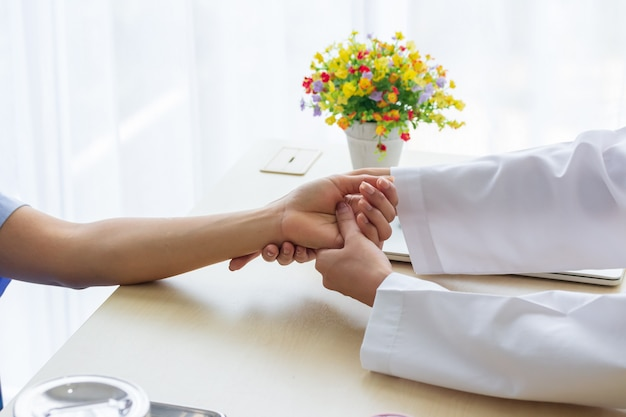 Beautiful female doctor holding patient's hand