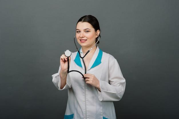 Красивая женщина-врач в защитной маске смотрит в сторону и о чем-то думает.