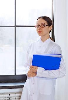 창 근처에 폴더가 서 있는 흰색 코트를 입은 아름다운 여성 의사.