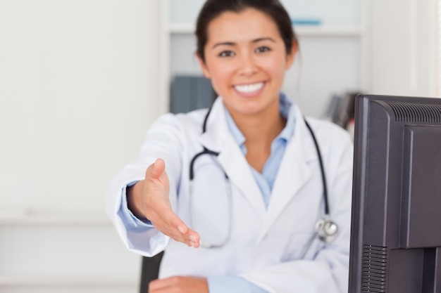 Beautiful female doctor inviting somebody to seat while looking at the camera