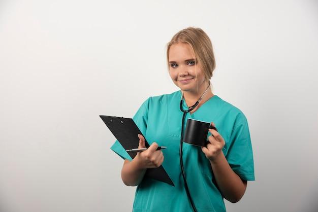 クリップボードとカップでポーズをとる美しい女医師。