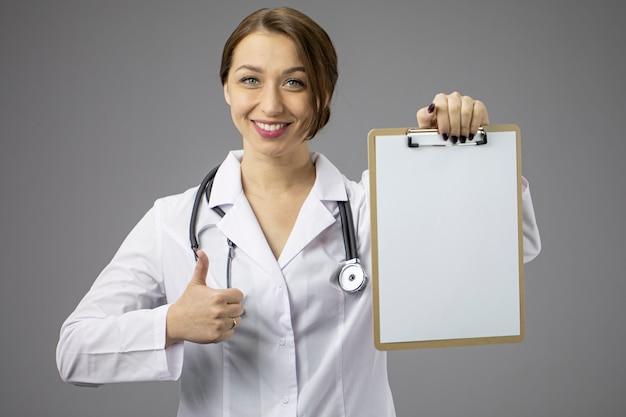 빈 클립 보드 표시, 복사 공간처럼 보여주는 아름 다운 여성 의사