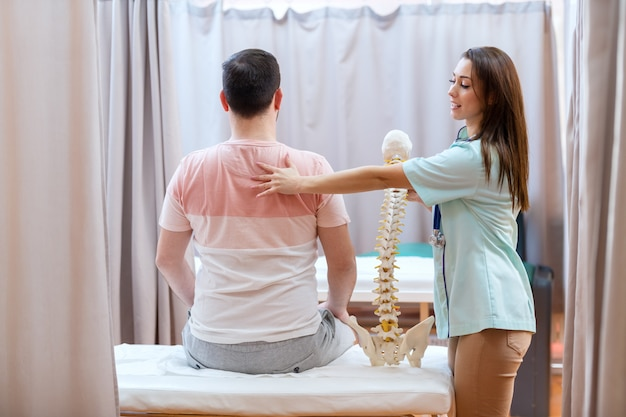 Beautiful female doctor with brown hair holding spine model and touching patient on his backs.