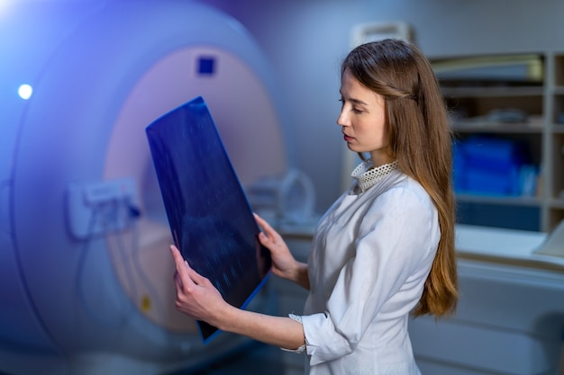 Beautiful female doctor with x-ray in hands. ct machine on background. radiology.