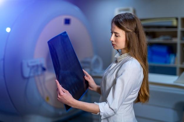 手にx線を持つ美しい女医。バックグラウンドでctマシン。放射線学。