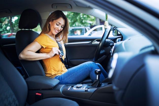 자동차를 운전하기 전에 안전 벨트를 씌우고 아름다운 여성 드라이버