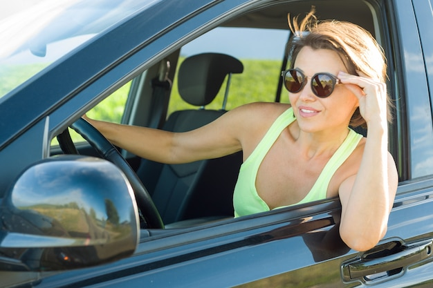 Beautiful female driver smiling while driving his car