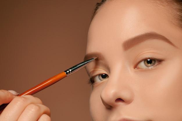 Красивые женские глаза с макияжем и кистью на фоне студии