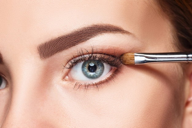 메이크업과 흰색 브러시와 아름 다운 여성의 눈
